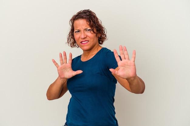 Mulher latina de meia-idade isolada no fundo branco, rejeitando alguém mostrando um gesto de nojo.