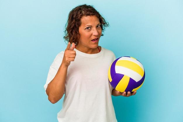 Mulher latina de meia idade jogando vôlei isolado no fundo azul, tendo uma ideia, o conceito de inspiração.