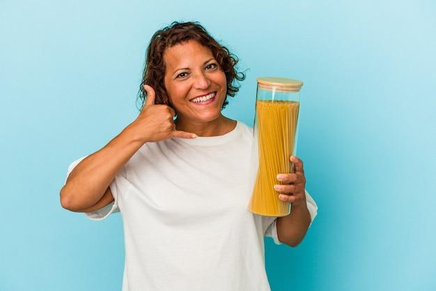 Mulher latina de meia-idade segurando o frasco de macarrão isolado em um fundo azul, mostrando um gesto de chamada de telefone móvel com os dedos.