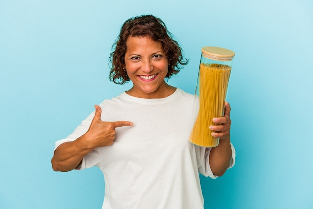 Mulher latina de meia-idade segurando um pote de macarrão isolado em um fundo azul pessoa apontando com a mão para um espaço de cópia de camisa, orgulhosa e confiante