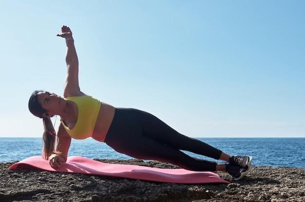 Mulher latina de meia-idade, vestindo roupas esportivas, treinando, fazendo exercícios físicos, prancha, abdominais, passo de alpinista, queimando calorias, mantendo a forma, ao ar livre à beira-mar, usando fones de ouvido, relógio inteligente