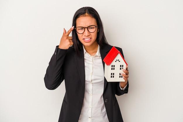 Mulher latina de negócios jovem segurando uma casa de brinquedo isolada no fundo branco, mostrando um gesto de decepção com o dedo indicador.