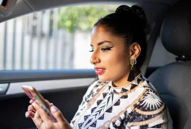 Mulher latina dentro de um carro usando seu telefone