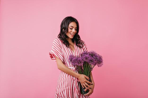 Mulher latina encantadora com carinho olha para o buquê de flores roxas selvagens. menina de vestido listrado envergonhada posando.