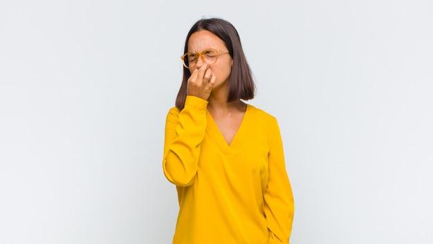 Mulher latina enojada, segurando o nariz para evitar cheirar um fedor desagradável