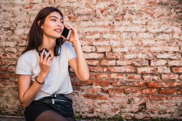 Mulher latina falando ao telefone.