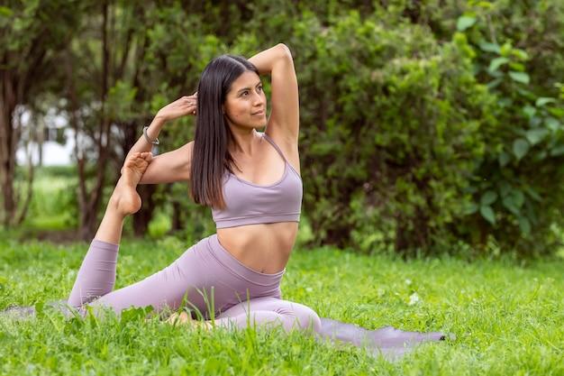 Mulher latina fazendo asanas de ioga com posturas diferentes em um parque ao ar livre com grama