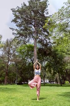 Mulher latina fazendo yogaasanas com posturas diferentes no parque ao ar livre com grama e árvores no ...