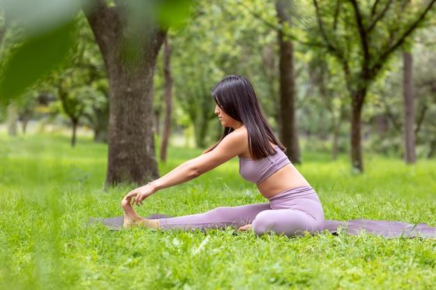 Mulher latina fazendo yogaasanas com posturas diferentes no parque ao ar livre com grama