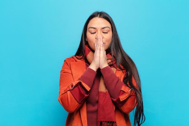 Mulher latina feliz e excitada, surpresa e maravilhada cobrindo a boca com as mãos, rindo com uma expressão fofa
