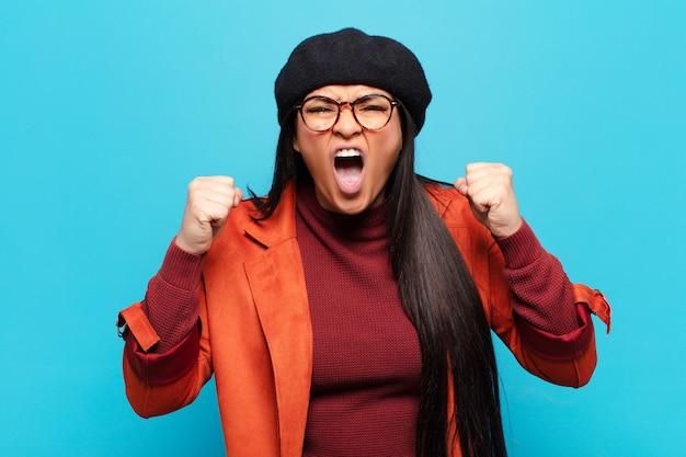 Mulher latina gritando agressivamente com uma expressão de raiva ou com os punhos cerrados celebrando o sucesso