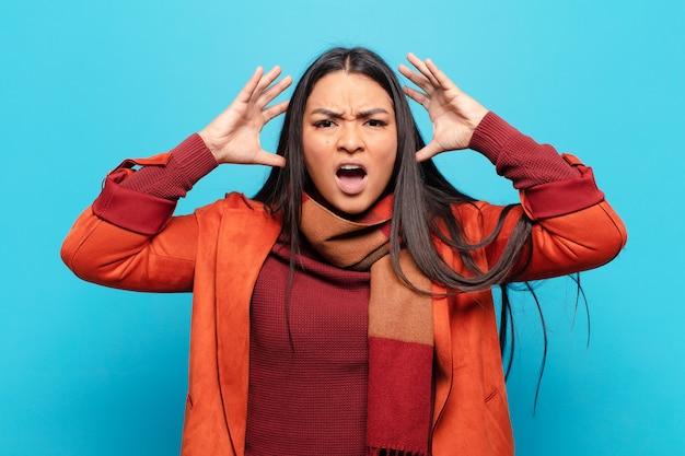 Mulher latina gritando com as mãos para o alto, sentindo-se furiosa, frustrada, estressada e chateada