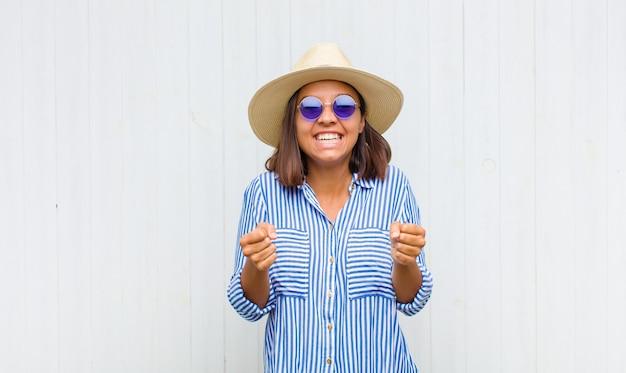 Mulher latina gritando triunfantemente, rindo e se sentindo feliz e animada enquanto celebra o sucesso