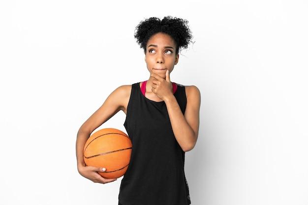 Mulher latina jovem jogador de basquete isolada no fundo branco tendo dúvidas e pensando