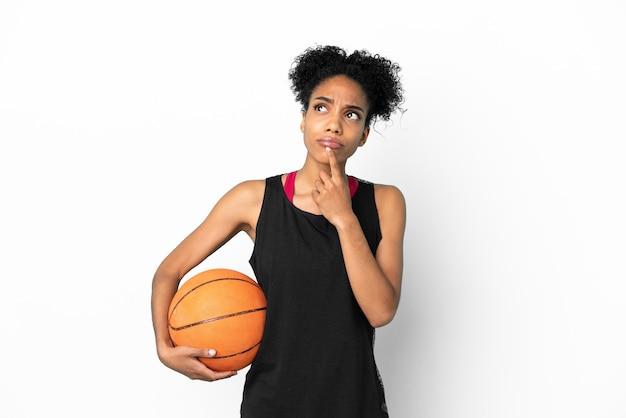 Mulher latina jovem jogador de basquete isolada no fundo branco tendo dúvidas enquanto olha para cima