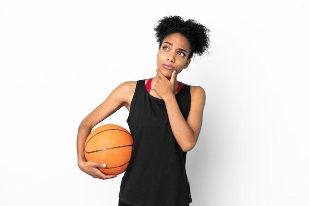 Mulher latina jovem jogador de basquete isolada no fundo branco tendo dúvidas