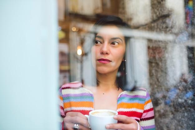 Mulher latina jovem olhando pela janela de uma loja de café enquanto bebe uma xícara de café.