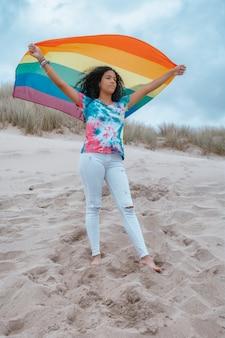 Mulher latina lésbica na praia segurando arco-íris bandeira orgulho