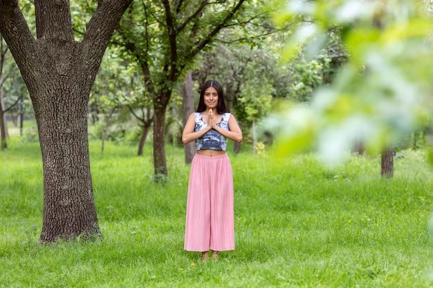 Mulher latina meditando ao lado de uma árvore no parque, na grama verde, com uma roupa rosa