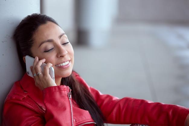Mulher latina na jaqueta vermelha, sorrindo enquanto fala ao telefone.