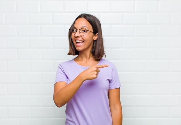 Mulher latina parecendo animada e surpresa apontando para o lado e para cima para copiar o espaço