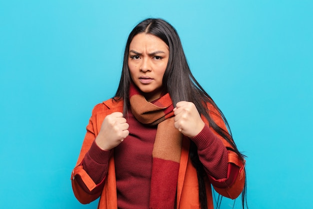 Mulher latina parecendo confiante, zangada, forte e agressiva, com punhos prontos para lutar em posição de boxe