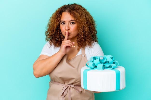 Mulher latina pastelaria jovem segurando um bolo isolado sobre fundo azul, mantendo um segredo ou pedindo silêncio.