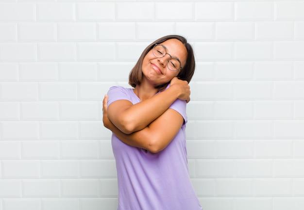 Mulher latina se sentindo apaixonada, sorrindo, se abraçando e se abraçando, permanecendo solteira, sendo egoísta e egocêntrica