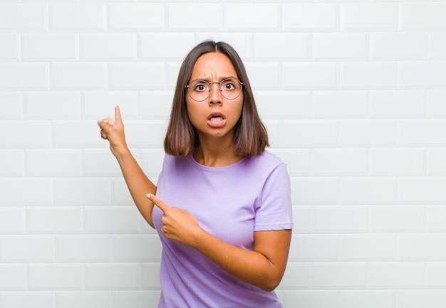 Mulher latina se sentindo chocada e surpresa, apontando para um espaço de cópia ao lado com olhar surpreso e boquiaberto