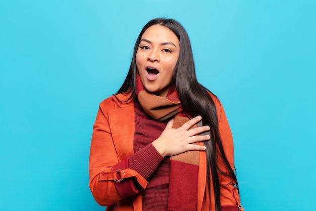 Mulher latina se sentindo chocada e surpresa, sorrindo, levando a mão ao coração, feliz por ser a única ou demonstrando gratidão