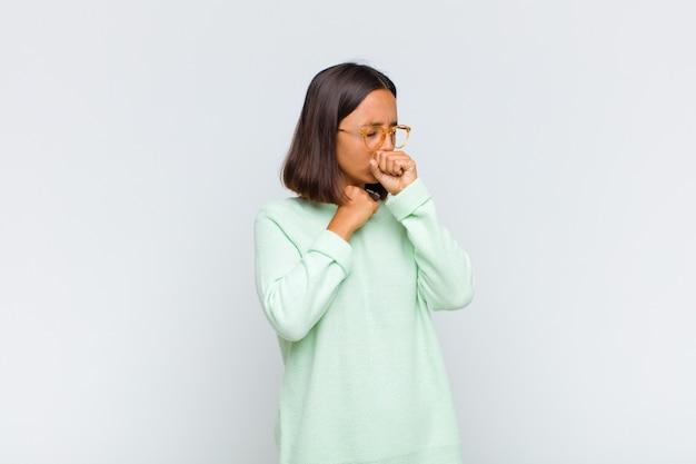 Mulher latina se sentindo mal com dor de garganta e sintomas de gripe, tosse com a boca coberta