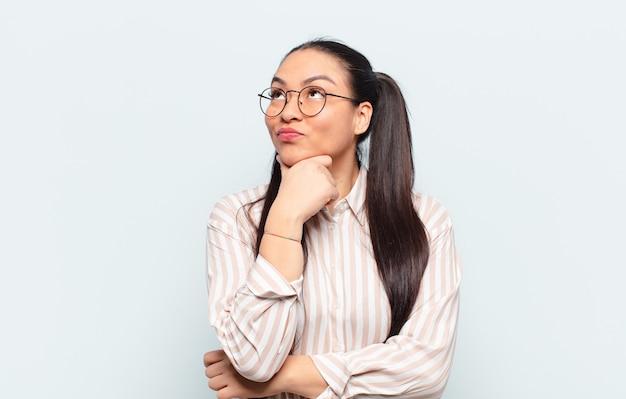 Mulher latina se sentindo pensativa, imaginando ou imaginando ideias, sonhando acordada e olhando para cima para copiar o espaço