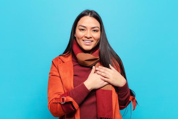 Mulher latina se sentindo romântica, feliz e apaixonada, sorrindo alegremente e segurando o coração de mãos dadas