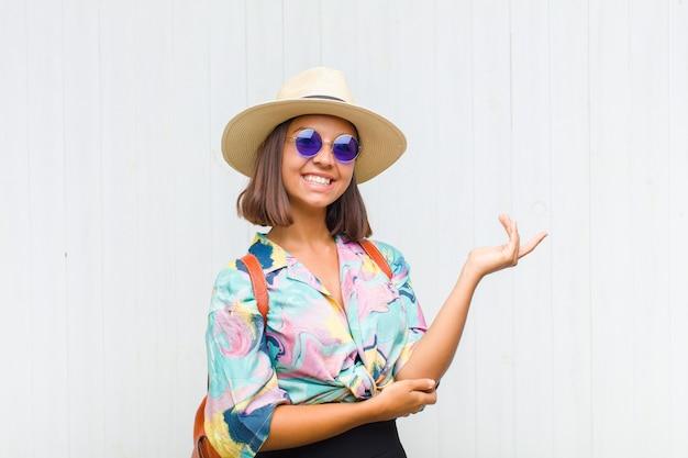 Mulher latina sorrindo com orgulho e confiança, sentindo-se feliz e satisfeita e mostrando um conceito no espaço da cópia