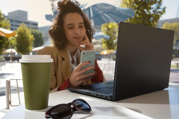 Mulher latina sorrindo, fazendo uma pausa durante o trabalho, selecione o foco no café e óculos escuros, com espaço de cópia