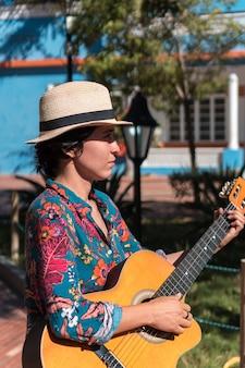 Mulher latina tocando violão, em pé no parque