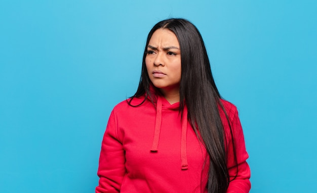 Mulher latina triste, chateada ou com raiva e olhando para o lado com uma atitude negativa, franzindo a testa em desacordo