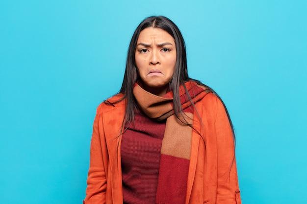 Mulher latina triste e estressada, chateada com uma surpresa ruim, com olhar negativo e ansioso