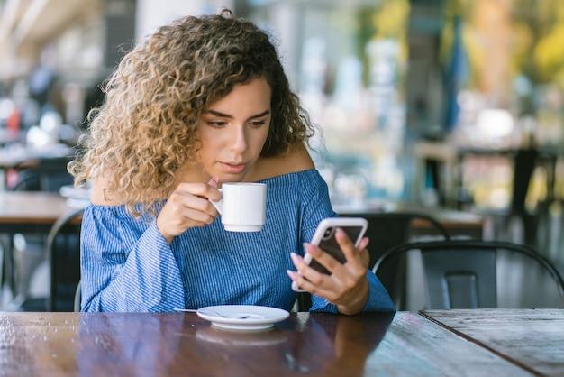 Mulher latina usando um telefone celular enquanto está sentado em uma cafeteria.
