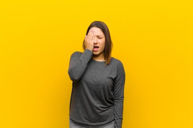 Mulher latino-americana com sono, entediada e bocejando, com dor de cabeça e uma mão cobrindo metade do rosto isolado contra a parede amarela