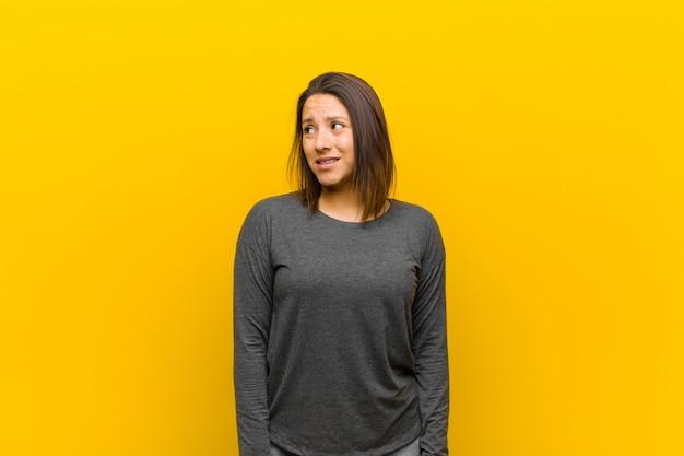 Mulher latino-americana, olhando preocupado, estressado, ansioso e assustado, em pânico e cerrando os dentes sobre parede amarela