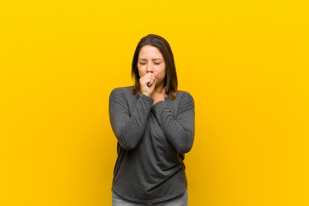 Mulher latino-americana que se sente doente com sintomas de dor de garganta e gripe, tosse com a boca coberta isolada