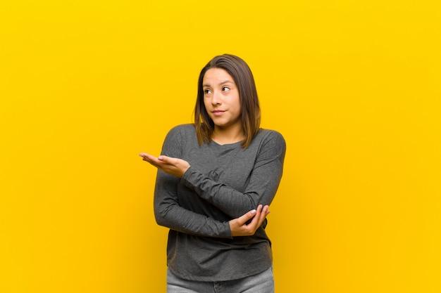 Mulher latino-americana se sentindo confusa e sem noção, pensando em uma explicação ou pensamento duvidoso sobre o muro amarelo