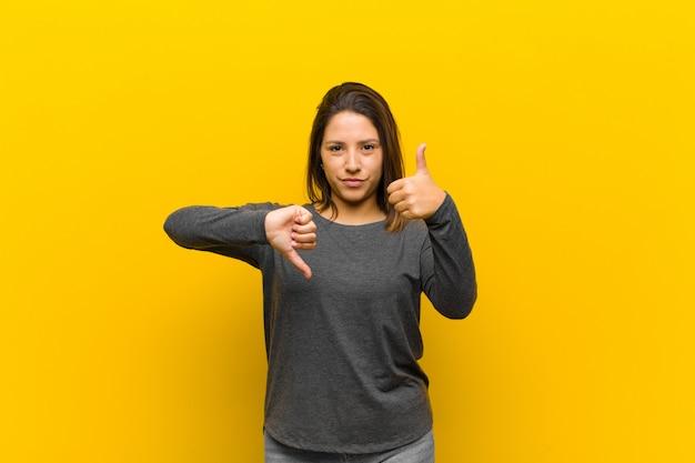 Mulher latino-americana se sentindo confusa, sem noção e insegura, ponderando o bom e o ruim em diferentes opções ou escolhas isoladas contra a parede amarela
