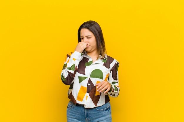 Mulher latino-americana sentindo nojo, segurando o nariz para evitar cheirar um fedor sujo e desagradável isolado contra a parede amarela