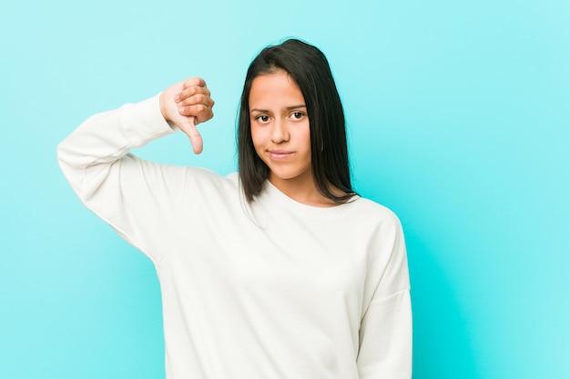 Mulher latino-americano bonita nova que mostra um gesto do desagrado, polegares para baixo. conceito de desacordo.
