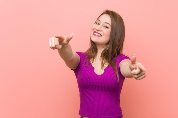 Mulher latino-americano nova contra os sorrisos alegres de uma parede cor-de-rosa que apontam para frontear.