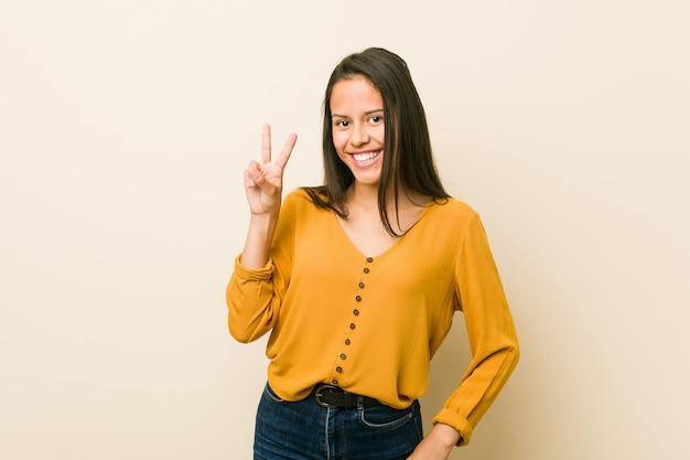 Mulher latino-americano nova contra um fundo bege que mostra o sinal da vitória e que sorri amplamente.
