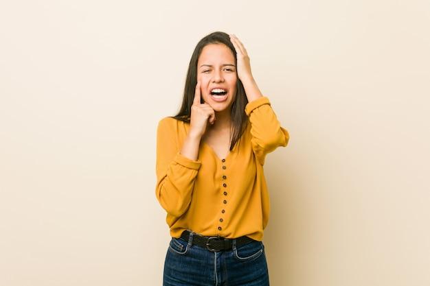 Mulher latino-americano nova contra uma parede bege que lamentam-se e que choram desconsoladamente.