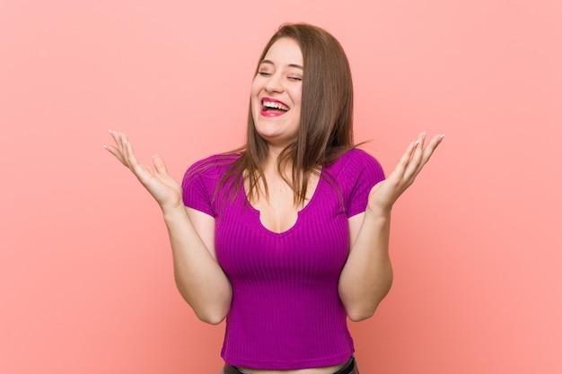 Mulher latino-americano nova contra uma parede cor-de-rosa alegre que ri muito. felicidade.